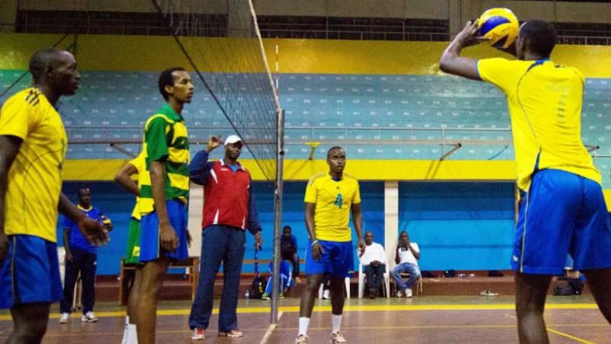 Head coah Paul Bitok (in red jacket) watches on during the team's training session early this week at Amahoro indoor stadium. (Timothy Kisambira)