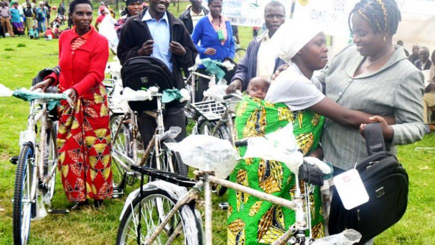 Angel Mukaminani, Nyabihu vice mayor for economic affairs (R), awards community mobilisers in savings culture with a bicycle. (Jean d'Amour Mbonyinshuti)
