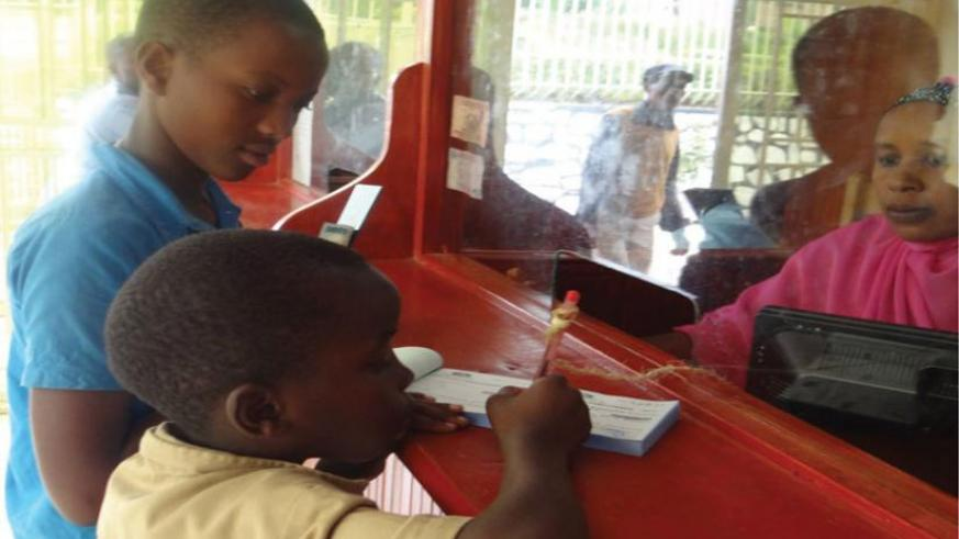 A young saver fills a form to deposit money at a city bank recently.