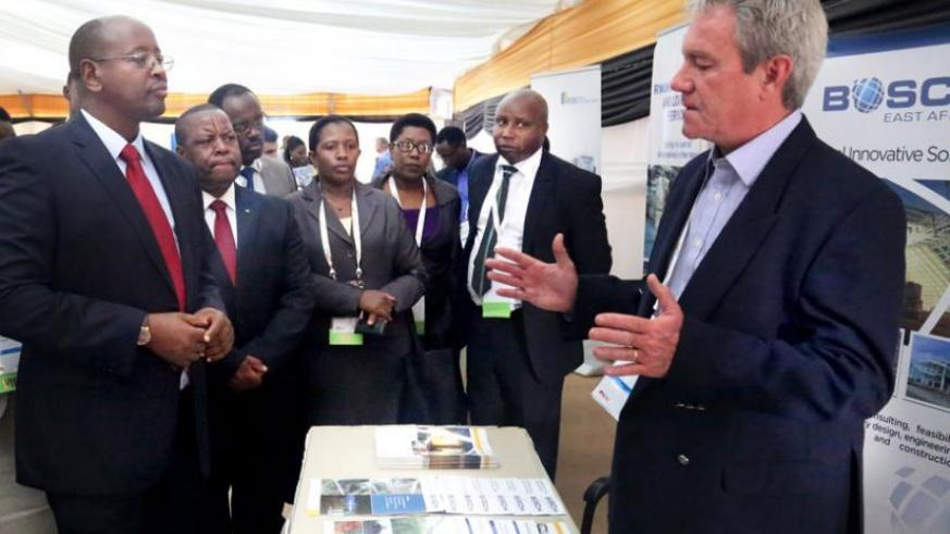 The Minister for Infrastructure, James Musoni (L), listens to Butch Carr, the energy director at Bosch projects, as other officials look on at the power and infrastructure investment forum in Kigali yesterday. (John Mbanda)