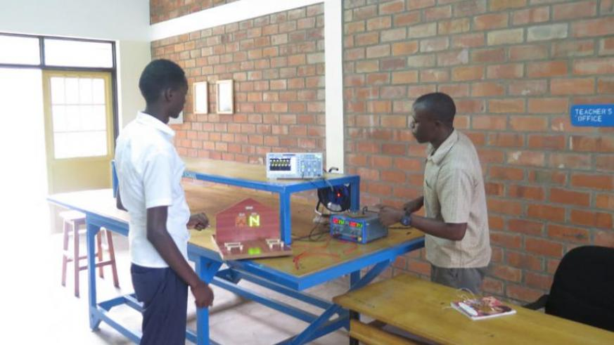 Kamuhanda explains to a student how it is done. He says there are plenty of opportunities that can earn a technician good money. (Arnold Agaba)