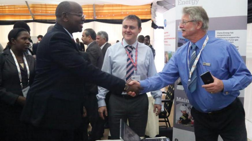 Minister for Infrastructure James Musoni (left), greets Paul de Mattos (right), the managing director of Clarke Energy, as Alex Marshall, the company's marketing manager looks on during the power and infrastructure investment forum held in Kigali on Monday. (John Mbanda)