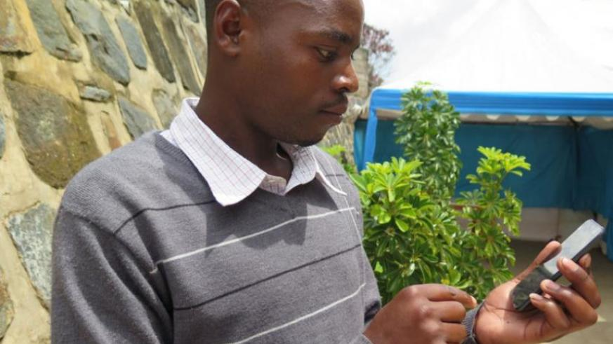 Alphonse Munyaneza, an English teacher, uses one of the  iPods distributed under TSLA project. (Stephen Rwembeho)