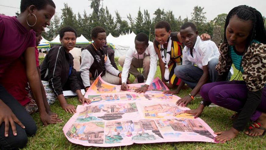Children from Kicukiro District discuss an art piece they were due to present in a competition at Redcross offices in Kigali yesterday. (Timothy Kisambira)