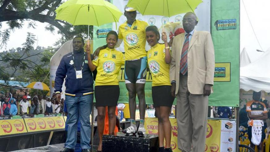 Ndayisenga relishes the moment after retaining the iconic Yellow Jersey which was bestowed upon him by Senator Chrysologue Karangwa (right) after finishing a decent fourth in the tour's fourth stage. (Peter Kamasa)