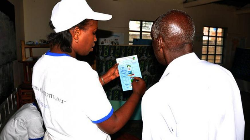 A returning officer guides an elderly man at a polling station in Kiyovu last year. (File)