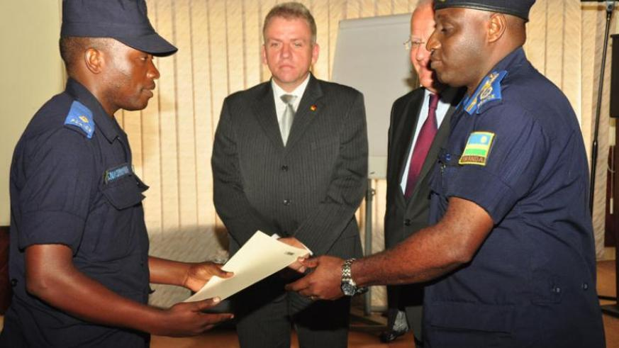 IGP Gasana gives a certificate to one of the Police trainees as German envoy Peter Fahrenholtz looks on. (Courtesy)
