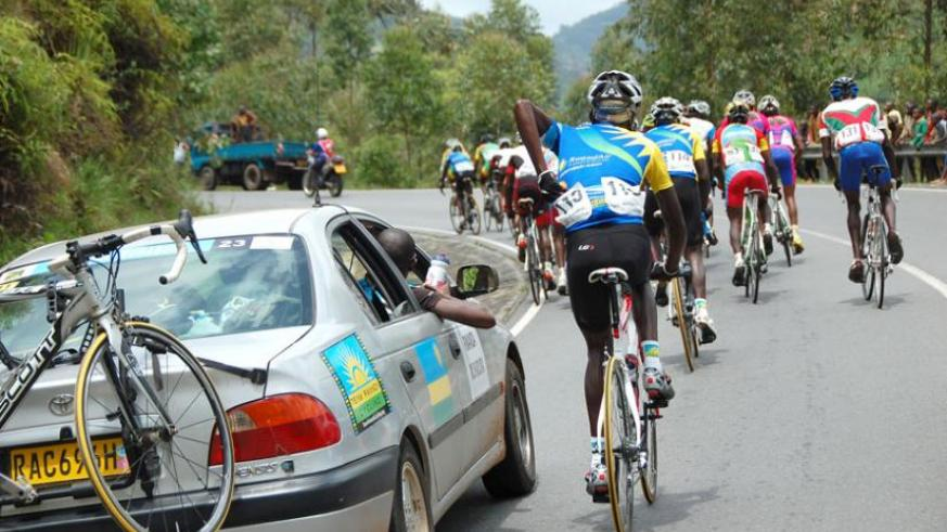 Aime Mupenzi, from Team Akagera tries to eat some bananas and take some water as the riders race to Rubavu during stage 5.