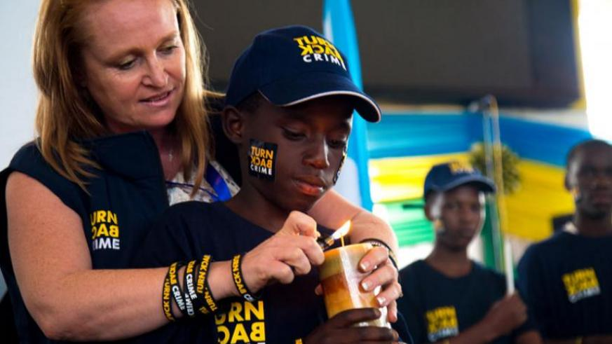 """The head of Communication at Interpol   Alison  Bernard, launches the """"Stop the Crime campaign with a child at Petit Stade yesterday. (Timothy Kisambira)"""