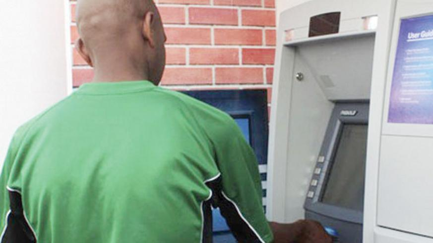 A person withdraws money from an ATM. (File)