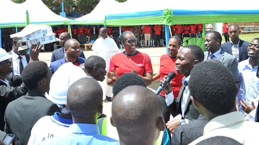Valens Ntirenganya leads a group of Imbuto scholars alumni in song as the First Lady Mrs. Jeannette Kagame joins in. (Courtesy)