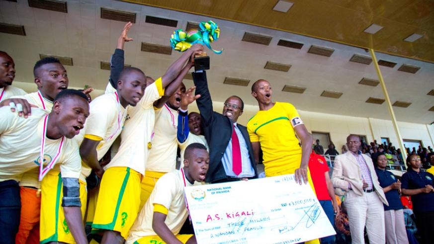 Kigali City Mayor Fidele Ndyisaba lifts the Ombudsman trophy while AS Kigali players show off the Rwf3m dummy cheque that they won after defeating Police 1-0. On the extreme right is Sports Minister Joseph Habineza and the Ombudsman Mrs. Aloysie Cyanzayire. (Timothy Kisambira)