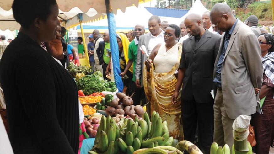 Kayonga (second, right) inspects horticulture products during the expo. (Peterson Tumwebaze)