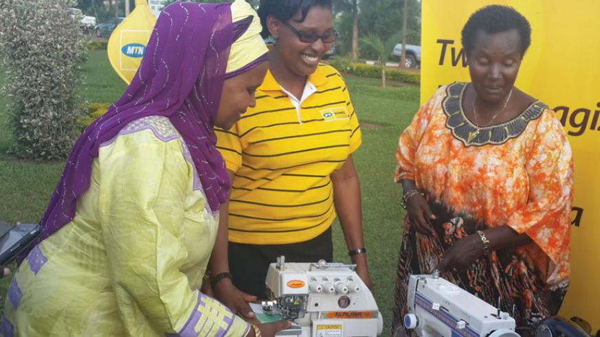 Mukarubega (left) is joined by Asiimwe to hand over some of the sewing machines to Nyiramanyana (right) at AVVAIS offices in Gahanga on Friday. (Donah Mbabazi)