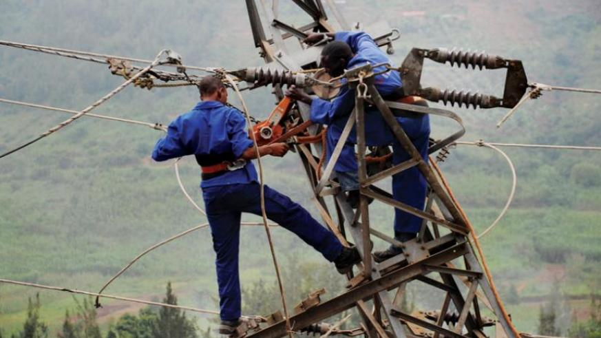 Workers fix a power line. Rwanda has signed an agreement to buy electricity from Kenya.