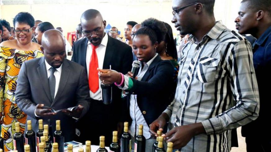 Youth and ICT minister Jean Philbert Nsengimana (L) and other officials look at pineapple wine made by Coprodemu, a Muhanga-based youth cooperative, during the annual 2014 YouthConnekt Convention at Petit Stade in Remera, Kigali, yesterday. (John Mbanda)