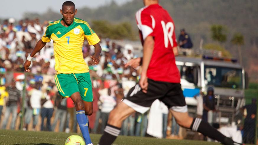Amavubi midfielder Jean-Baptiste Mugiraneza takes on a Libyan defender in the 2015 Afcon qualifier which Rwanda won 3-0. Rwanda has attained their best ever Fifa ranking jumping from 90th position to 68th. (File photo)