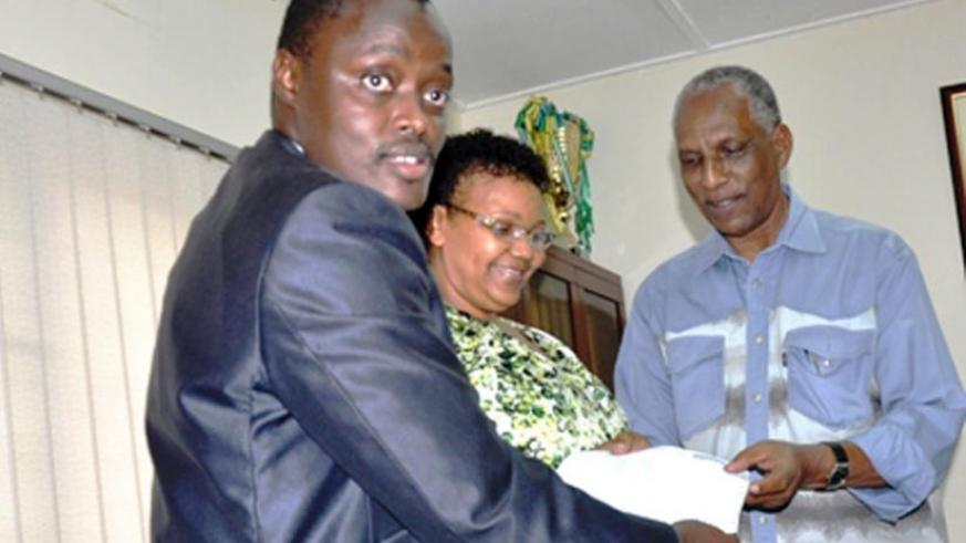 Kalisa (L) hands over the donation cheque to Sayinzoga as an unidentified woman looks on. (Courtesy)
