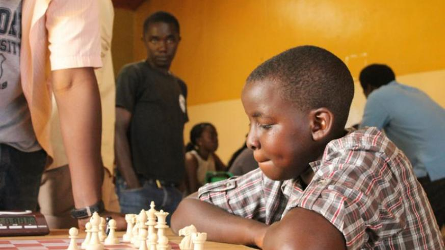 A young boy playing chess in a tournament early this year. Many children embraced the game this year. (F. Mugisha)