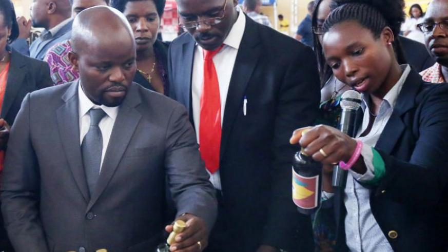 Nyiramajyambere explains to Youth and ICT minister Jean Philbert Nsengimana (left) and national youth council coordinator Norbert Shyerezo (centre) how pineapple wine is manufactured, during an exhibition in Kigali on December 17, 2014. (File)