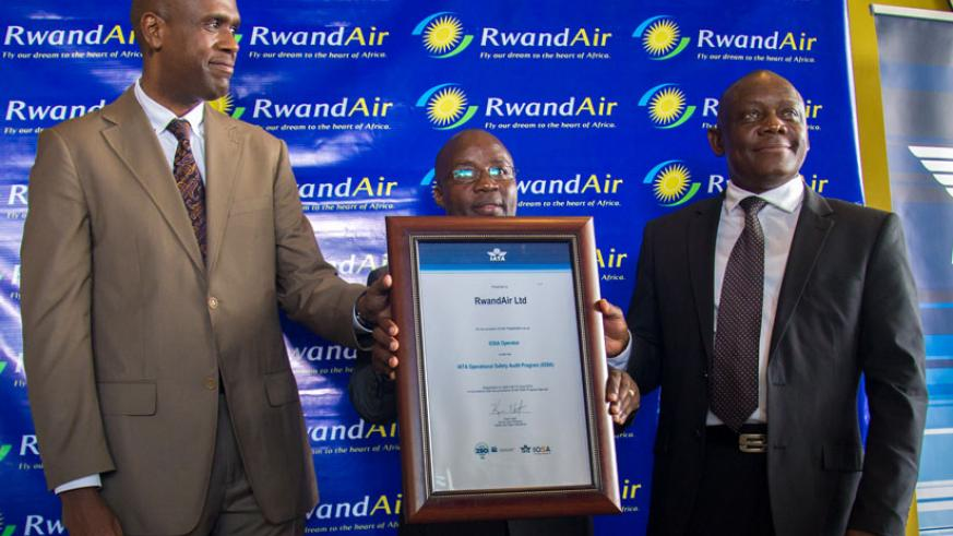 State minister in charge of Transport Dr.Alexis Nzahabwanimana (centre) and RwandAir CEO John Mirenge (left) after receiving a certificate from International Air Transport Association vice-president for Africa Raphael Kuuchi (right) recently. (Timothy Kisambira )