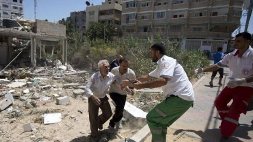 Palestinian medics help evacuate a survivor after an Israeli airstrike on his home in Gaza City on July 27, 2014. (Net)