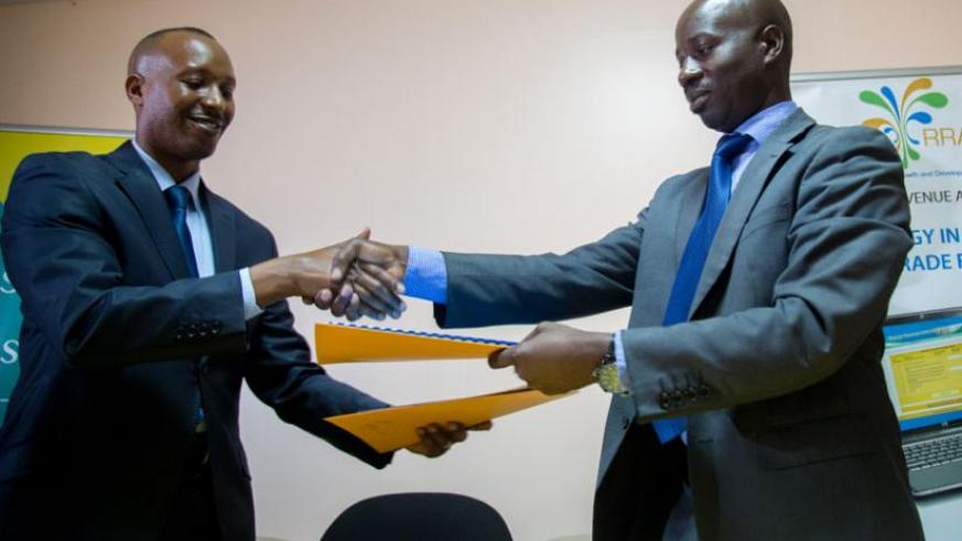 Seka (left) and Raphael Tugirumuremyi, the RRA Deputy Commissioner General in charge of customs exchange documents in Kigali on Monday. (Timothy Kisambira)