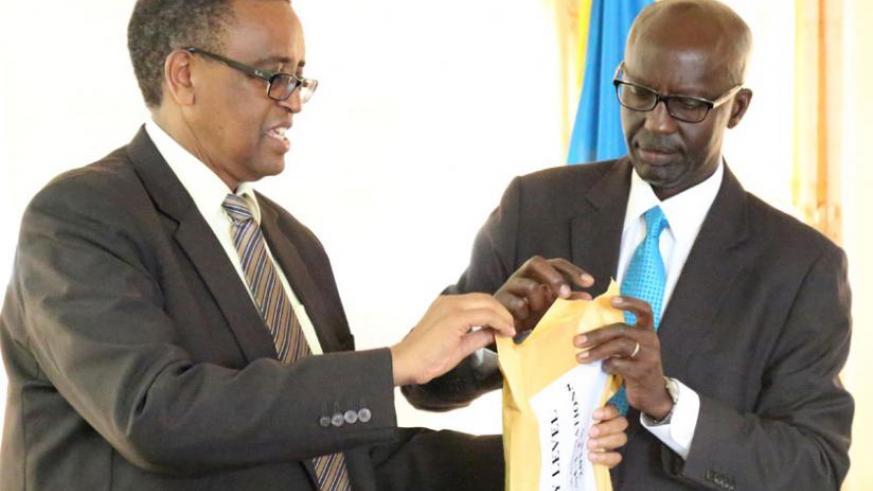 Education minister Silas Lwakabamba (L) and John Rutayisire, the director-general of Reb, open an envelope containing the 2014 O-Level results on Monday. (John Mbanda)