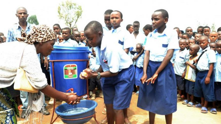 A woman joins Kagugu Primary School children in washing hands in 2012. Mineduc has launched a new school health policy and strategic action plan. (File)
