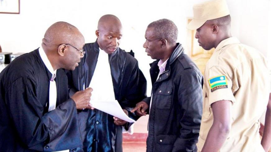 Bandora (R) consults with his lawyers Boniface Nizeyimana (C) and Ferdinand Mbera  after a court session in May 2013. (File)
