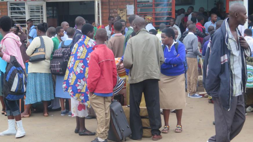 Students wait for their respective buses as others (in the background on the right) struggle to buy tickets. (Solomon Asaba)