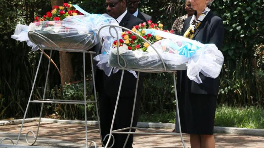 Lagarde (right), with Finance minister Claver Gatete, lays a wreath on one of the mass graves at Kigali Genocide memorial, yesterday. (John Mbanda)