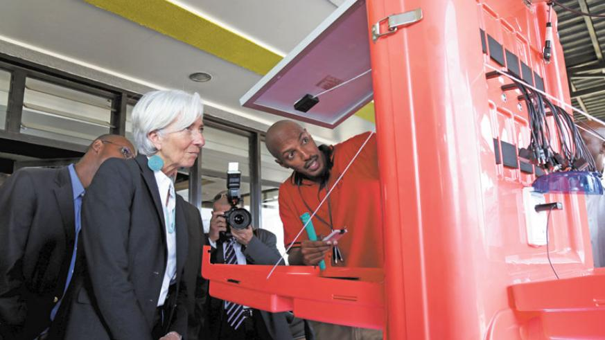 IMF Director General, Christine Lagarde (L) looks at a solar charger at kLab yesterday. (John Mbanda)