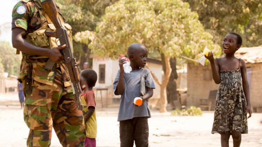 An RDF peacekeeper interacts with children in Bangui. (Timothy Kisambira)