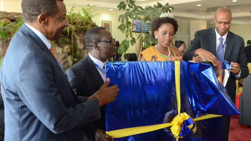 Uganda's Transport minister Eng. Abraham Byandala admires a gift presented to him by Mirenge (right) at Entebbe International Airport. Centre is Patricia Ntale, Uganda's Miss Tourism .