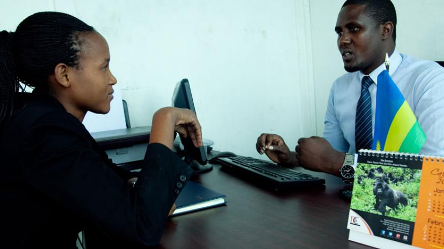 Komezusenge (right) talks to a client in his office recently. (Faustin Niyigena)