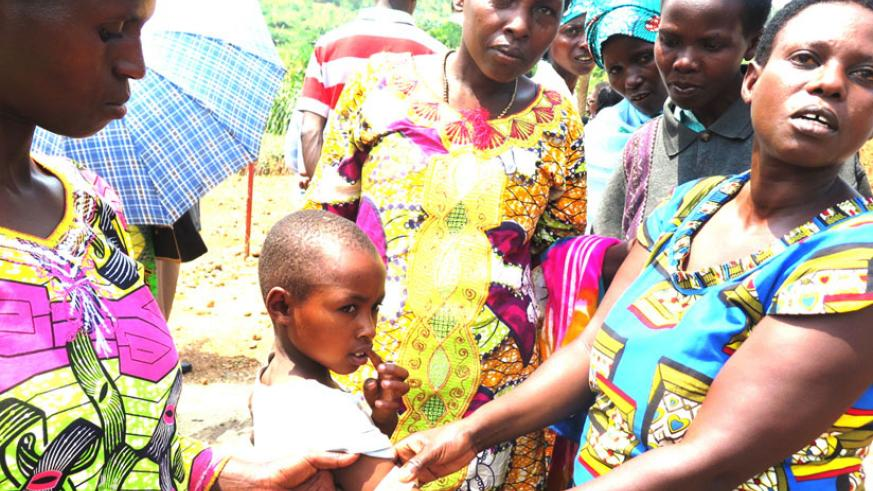 Community health workers demonstrate how the MUAC malnutrition test is done. (Stephen Rwembeho)