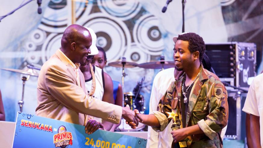 Jay Polly receives a dummy cheque from minister of sports and culture, Joe Habineza last year. Jay Polly was last year's winner of the Primus Guma Guma season 4 competition. He bagged Rwf 24m. (File)