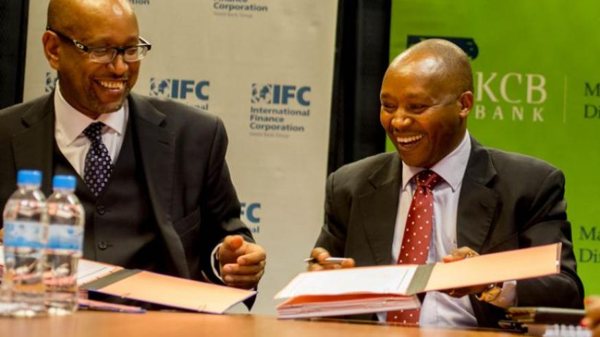Rwanda's Managing Directors of KCB Maurice Toroitich(R) s hare a light moment with Ethiopis Tafara, IFC vice president for corporate risk and sustainability. (T.Kisambira)