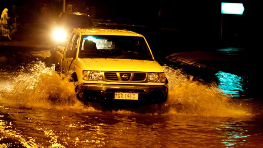 A motorist drives through a flooded street in downtown Kigali after the weekend downpour. (Timothy Kisambira)