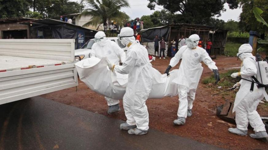 Liberian nurses remove an Ebola victim from a street on the outskirts of Monrovia Liberia last August . (Internet photo)
