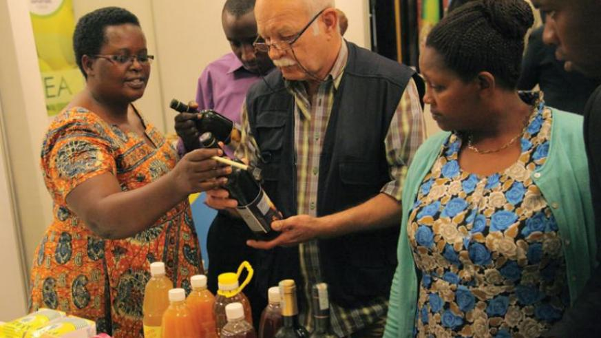 Christine Murebwayire (left) explains how she makes banana wine during a mini-exhibition at the Exporters' Forum last year. (File)