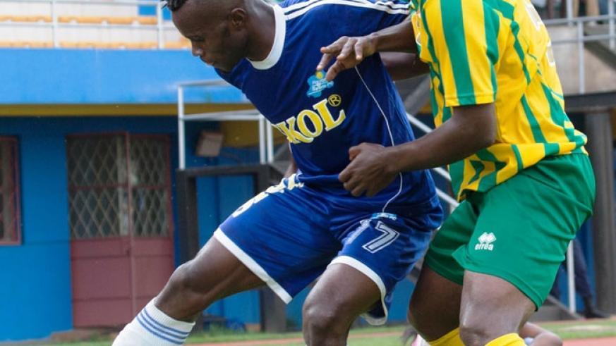 Rayon Sports striker Peter Otema (left) shields the ball against a Panthere defender on Sunday at Amahoro stadium. (Timothy Kisambira)