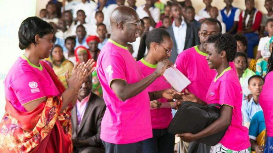 Prime Minister Anastase Murekezi awards best performing girls in last year's national examinations during the national Women's Day celebrations in Ngoma District yesterday. (Courtesy)