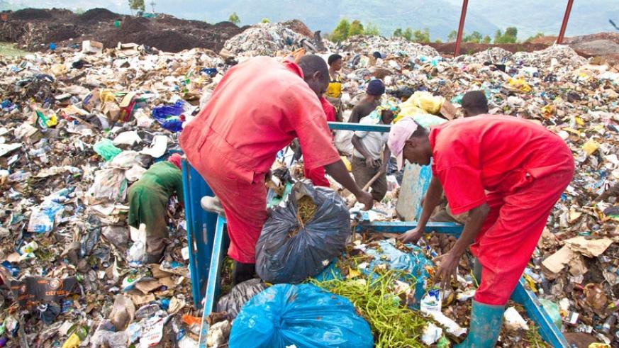 Workers at Nduba dumping site in Gasabo District offload Garbage recently. (Timothy Kisambira)