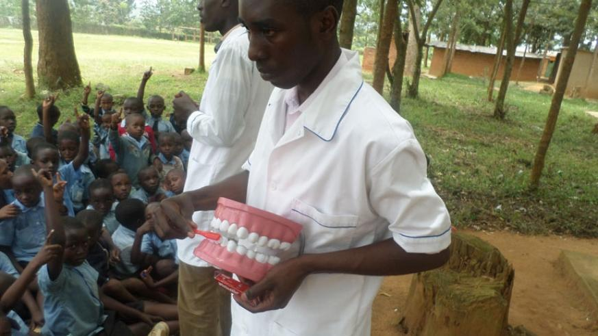 A dental medic demonstrates to pupils of Groupe Scolaire Nyamata Catholique, Bugesera District, how to brush teeth last year. (File)