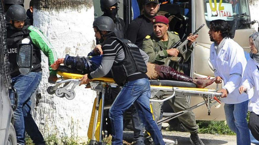 A person is taken away on a stretcher outside the Bardo Museum in Tunis, Tunisia.