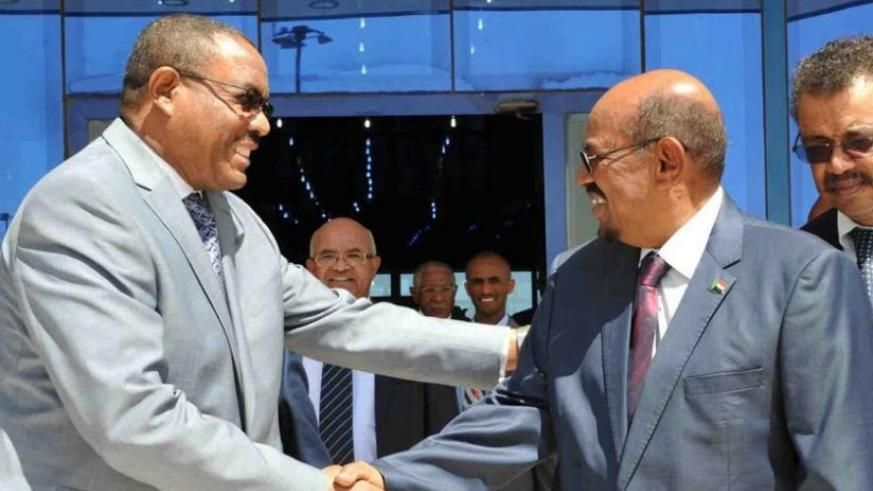 Ethiopian Prime Minister Desalegn, shakes hands with President Bashir (R) after the signing ceremony  in Khartoum on Monday. (Athan Tashobya)