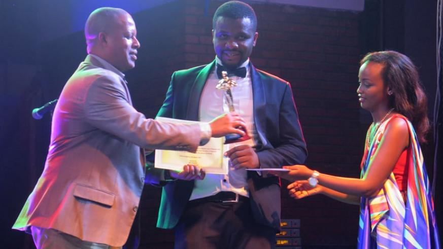 """Jerome Gasana, the Director General WDA, hands the Best Actor's award to Muniru Habiyakare for his exceptional role in the movie, """"Butorwa."""""""