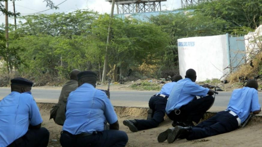 Kenyan police officers take cover outside the Garissa University College during an attack by gunmen.